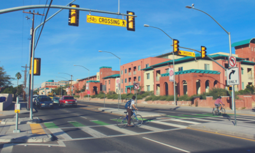 Cars stopping for man on bicycle at the enhanced bike and pedestrian crossing on 5th St & Euclid in Tucson