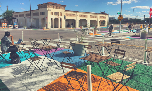 Complete streets demo project at 6th Ave & 7th St in Tucson. Brightly painted intersection murals, man working on computer at public table and chairs, bicyclists riding through intersection