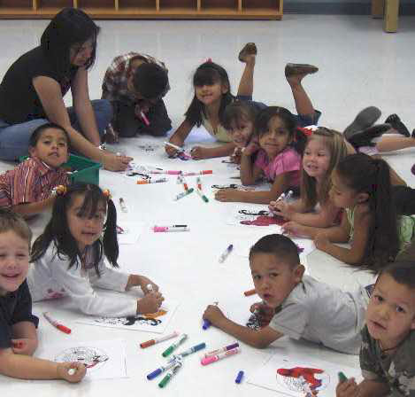 group of kids leaning on art paper