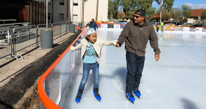 father and daughter ice skating in downtown tucson
