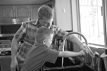 Man and child at kitchen sink